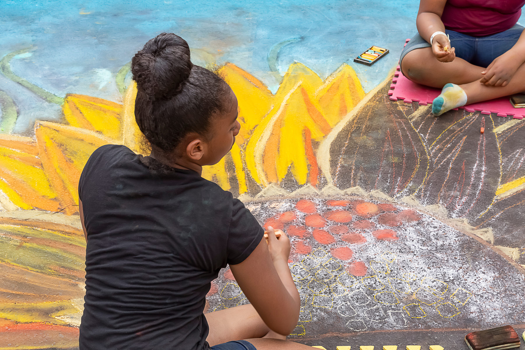 Kids drawing a large chalk art sunflower