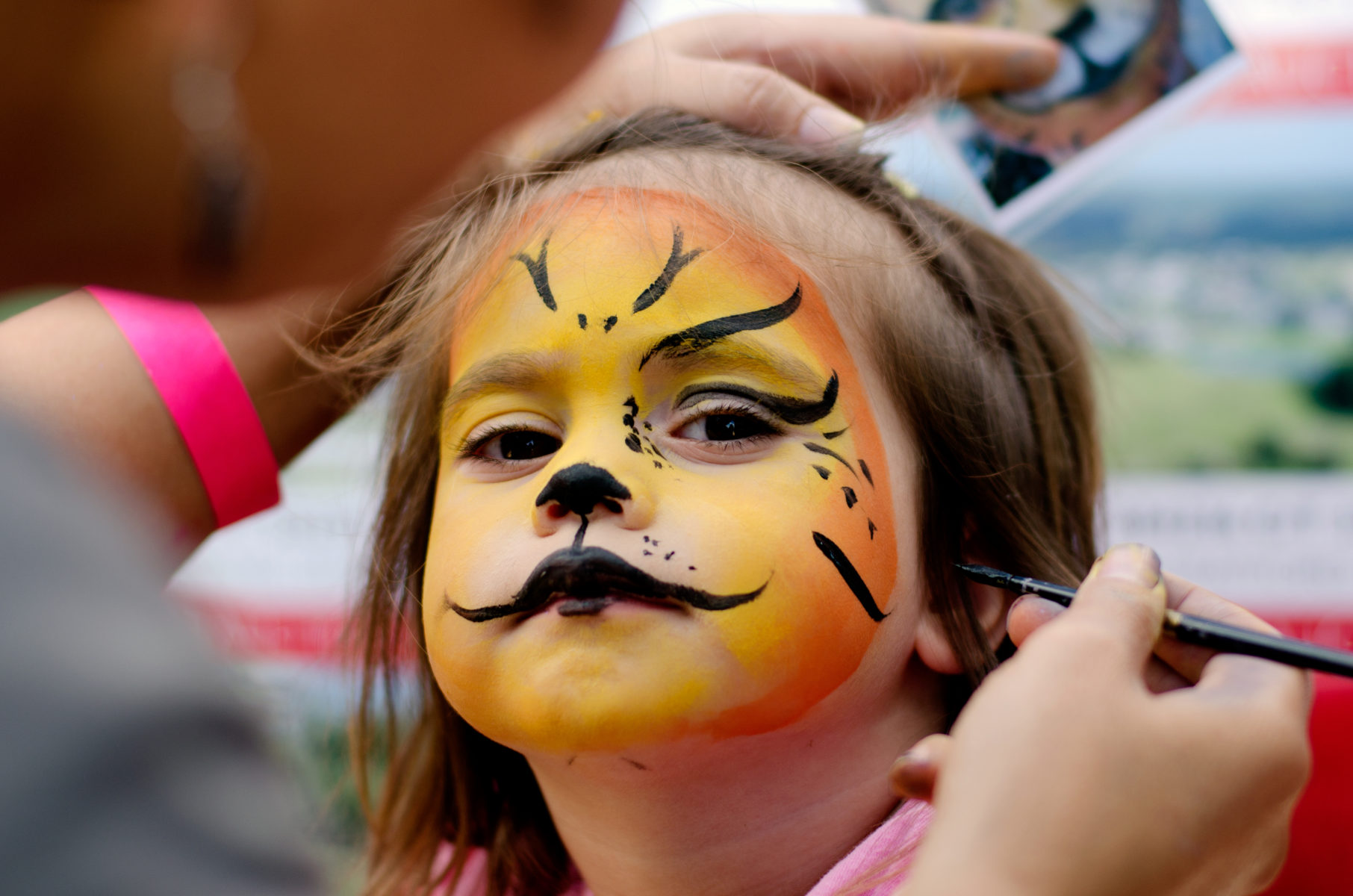 Young girl getting her face painted at art festival