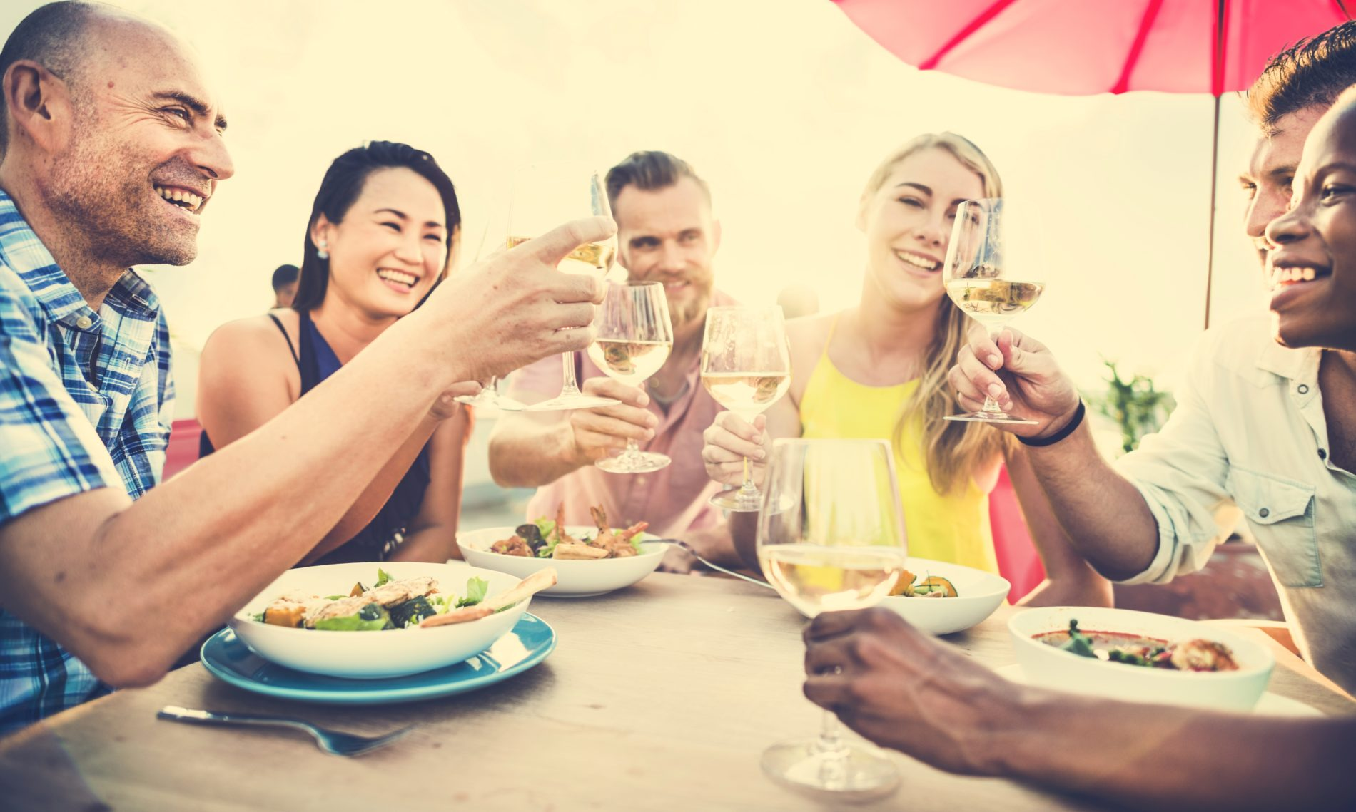 Group of happy friends dining outside on the beach