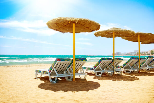 Row of shaded beach chairs in Marbella, Spain