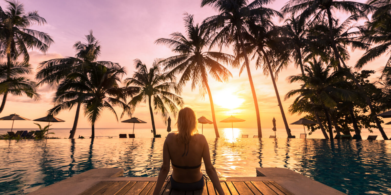 Woman relaxing by a pool with sunset and palm trees